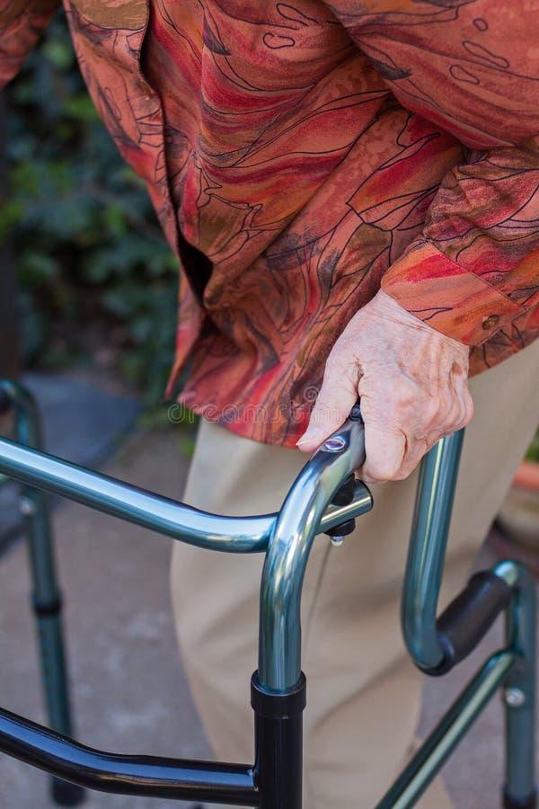 走与可折叠步行者的年长妇女 免版税库存图片
