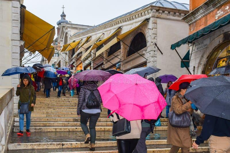 走与在威尼斯大石桥Bridge蓬特de威尼斯大石桥楼梯的伞的人们在威尼斯,意大利 免版税图库摄影