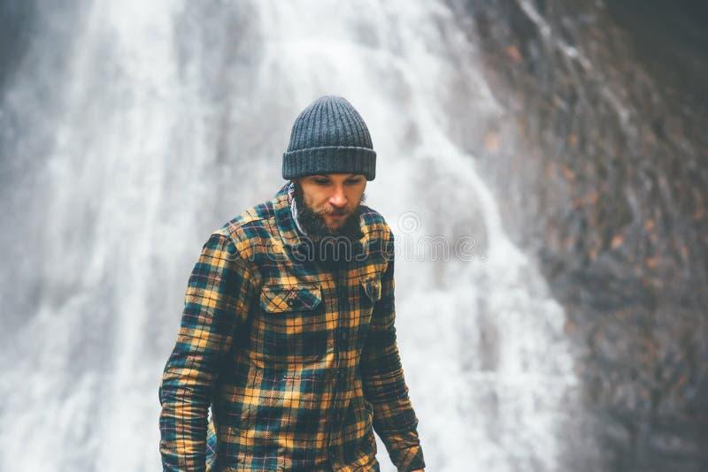 走与在背景的瀑布的有胡子的人 库存图片