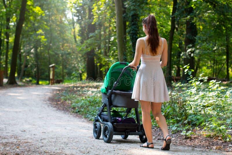 走与在自然forrest走道的婴儿推车的后面观点的可爱的妇女,年轻母亲外面以她新出生的婴孩 免版税库存照片