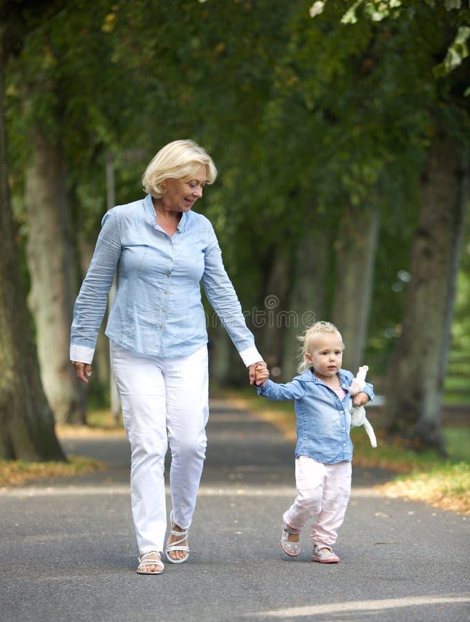 走与女婴的祖母在公园 免版税库存图片