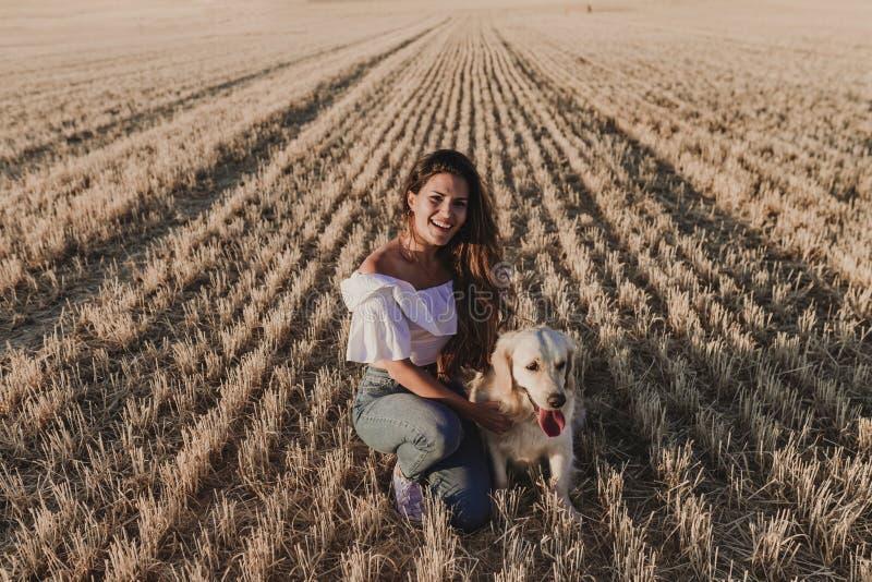 走与她的在一个黄色领域的金毛猎犬狗的年轻美女在日落 自然和生活方式户外 库存照片