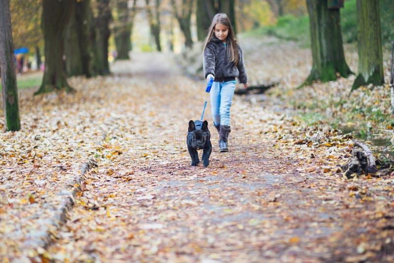 走与她的狗的小女孩 库存图片