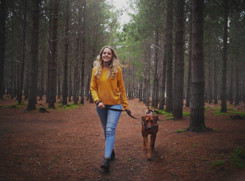 走与她的狗的年轻白肤金发的妇女在森林里 图库摄影