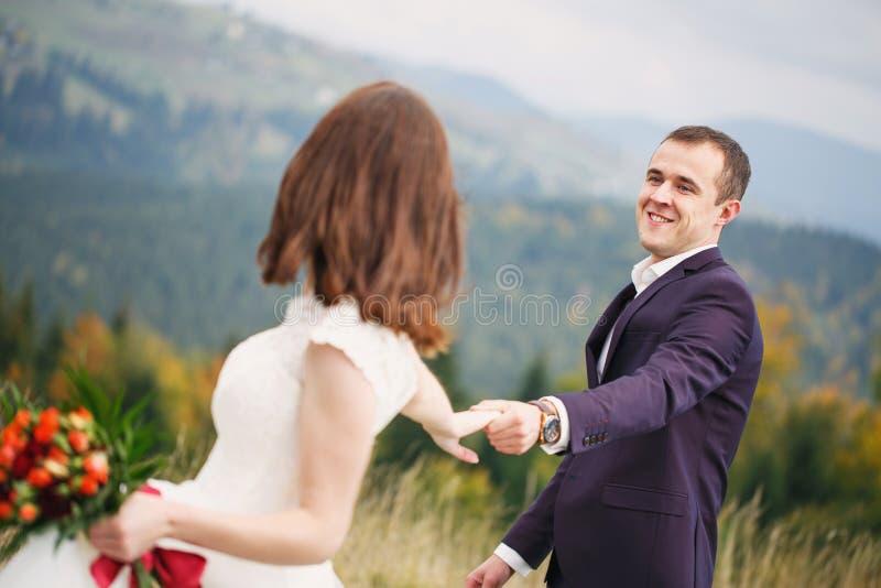 走与山草坪 喀尔巴阡山脉在背景中 新婚佳偶在婚礼之日 免版税库存图片