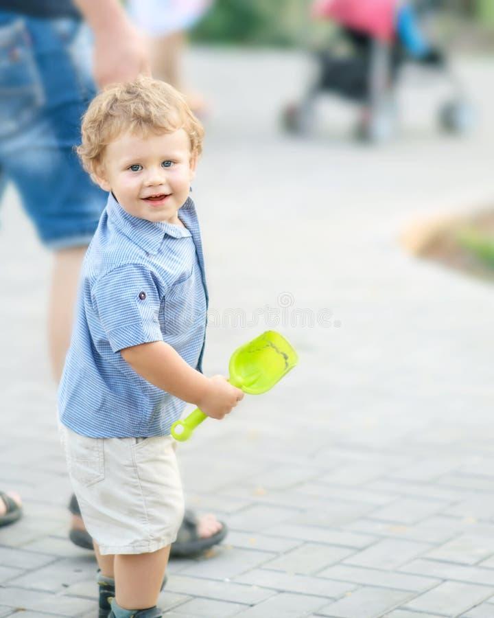 走与年轻父亲的一个愉快的微笑的男婴在夏天公园 与外面一个逗人喜爱的矮小的儿子的一个家庭 父母亲爱,父亲 库存图片