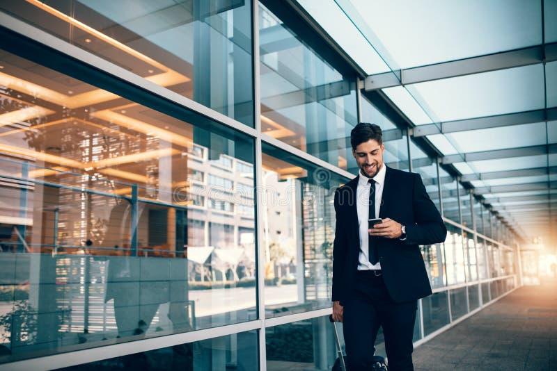 走与手机的年轻商人在机场 免版税图库摄影