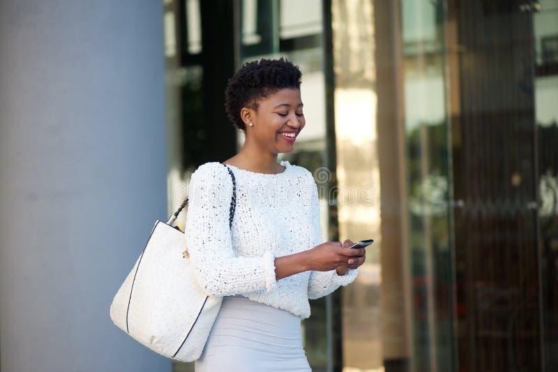 走与手机的现代妇女在城市 免版税图库摄影