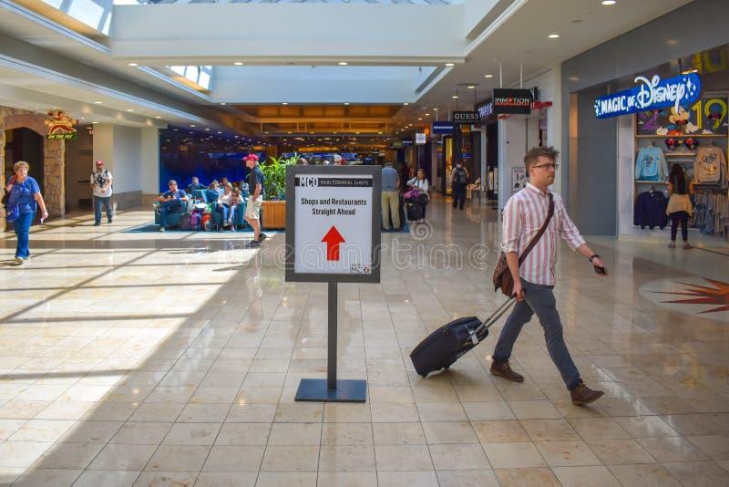 走与接近商店区域的行李的人在奥兰多国际机场1 库存照片