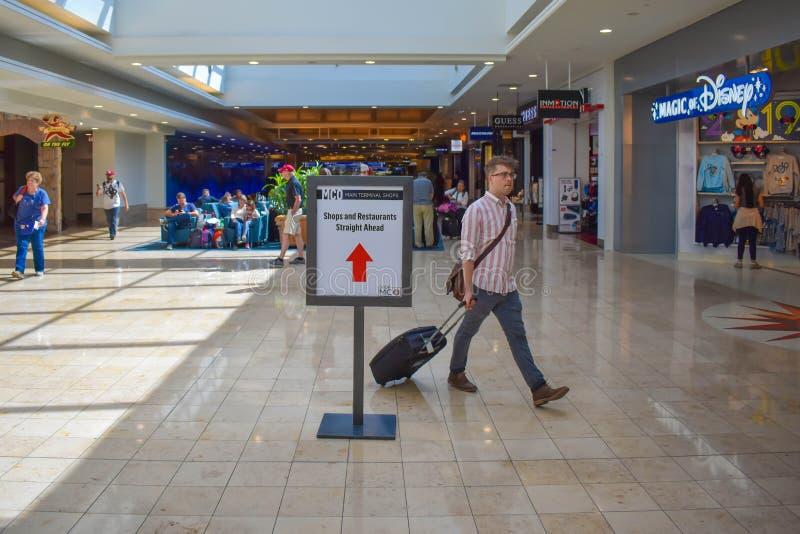 走与接近商店区域的行李的人在奥兰多国际机场3 免版税库存图片