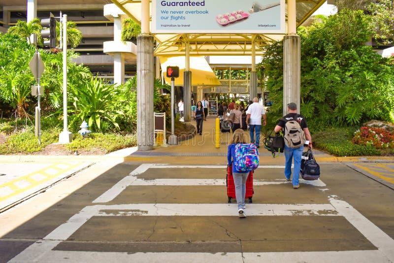 走与接近迪斯尼商店的行李的人们在奥兰多国际机场2 免版税库存图片