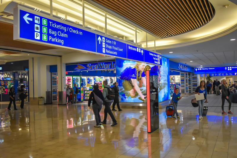 走与接近Seaworld商店和卖票和报到蓝色标志顶视图的行李的人们在奥兰多国际Airp 免版税库存图片