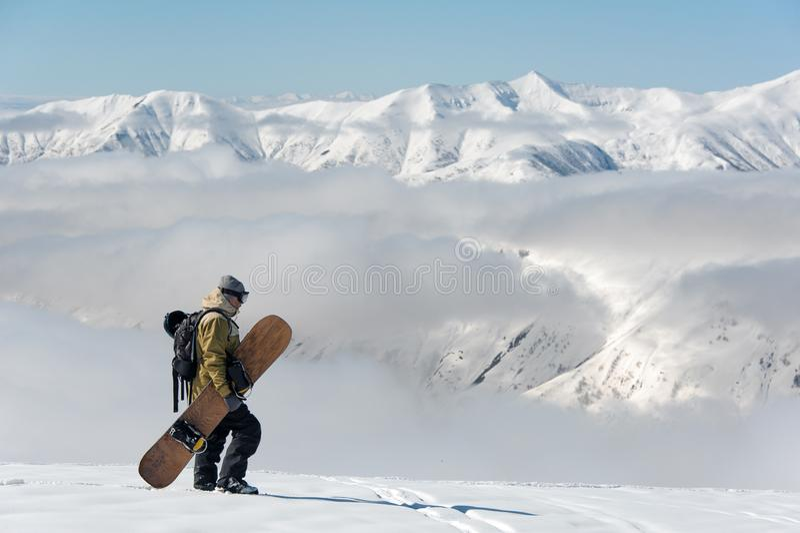 走与棕色雪板的人在山区度假村 免版税库存照片