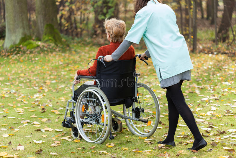 走与残疾夫人的护士 免版税图库摄影