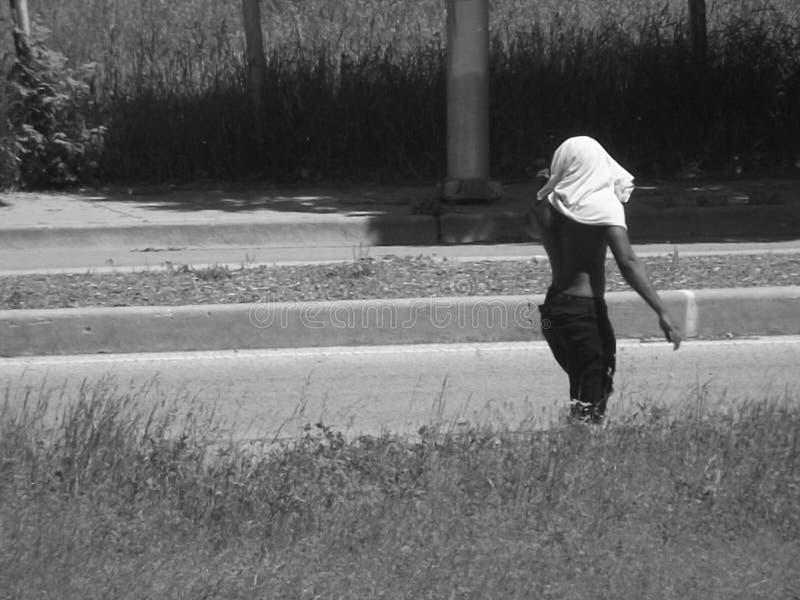 走与毛巾的人在它上面头 免版税库存图片