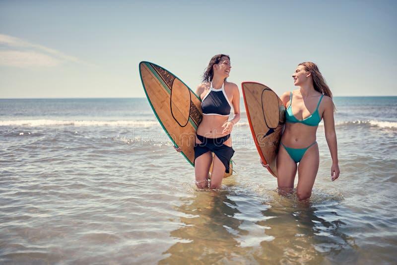 走与沙滩的委员会的微笑的冲浪者女孩 Surfe 免版税库存照片