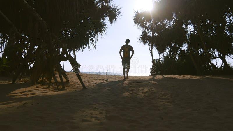 走与沿热带海滩的背包的年轻人到海洋 努力去做在含沙岸的男性远足者海 免版税库存图片