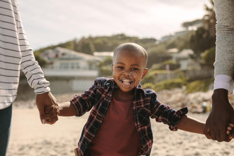 走与海滩的父母的微笑的男孩 免版税库存图片