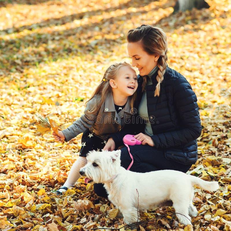 走与狗的幸福家庭在秋天公园 年轻母亲和女儿有白色狗的获得乐趣在落叶 秋天假日 免版税库存图片