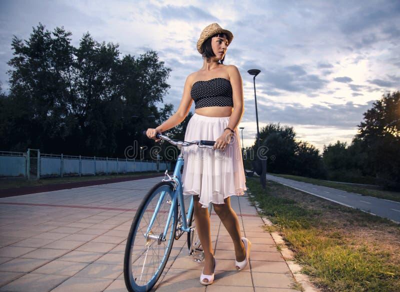 走与葡萄酒蓝色自行车的少妇 库存照片