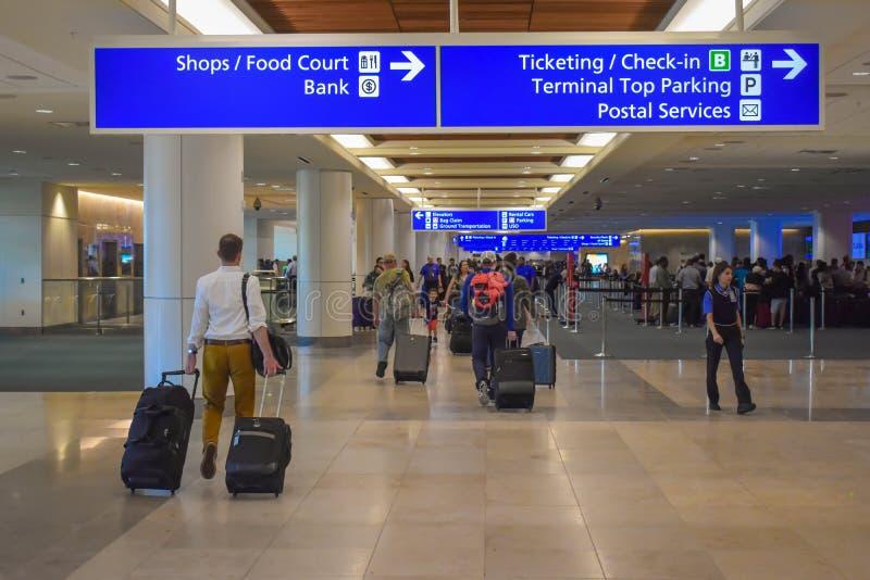 走与行李和终端B卖票和报到标志顶视图的人在奥兰多Internat奥兰多国际机场 免版税库存图片