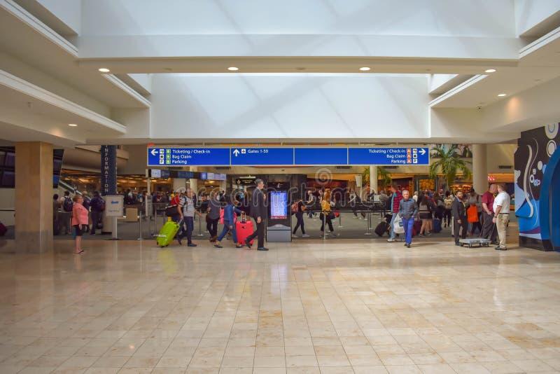 走与行李的人们到不同的终端和卖票和报到蓝色标志顶视图在奥兰多国际Airpo 免版税图库摄影