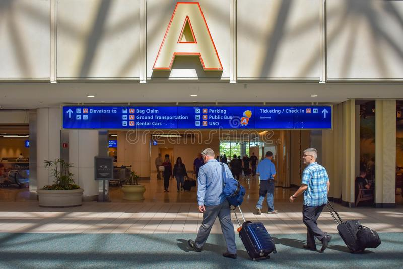 走与行李的人们在终端A地区在奥兰多国际机场5 库存照片