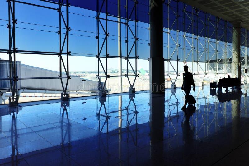 走与行李的人在机场 免版税库存图片