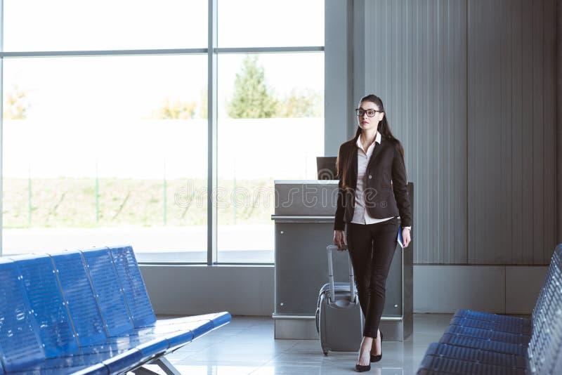 走与行李的年轻美丽的女实业家 免版税图库摄影