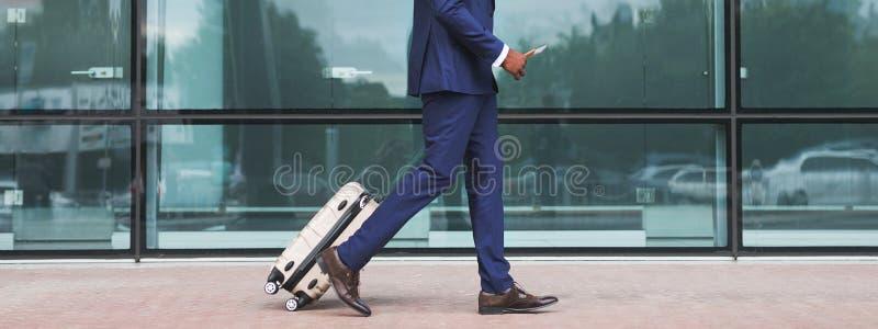 走与行李的非裔美国人的商人,抵达机场 免版税库存照片