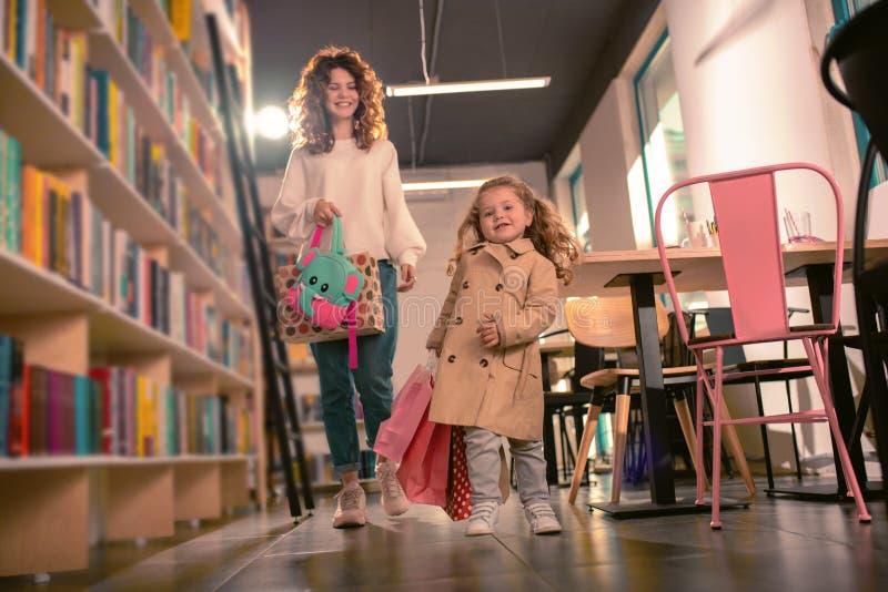 走与购物带来的喜悦的白肤金发的女孩 库存图片