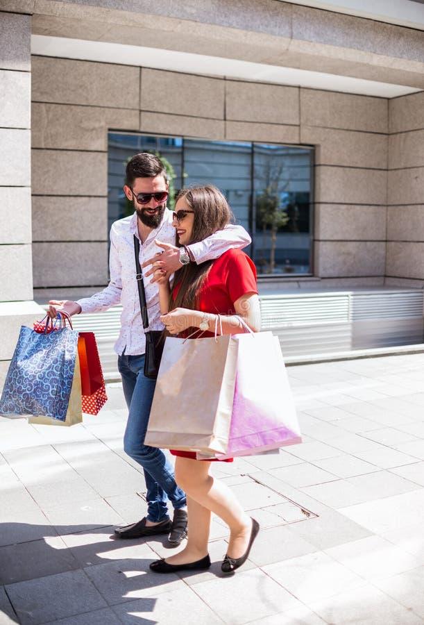 走与购物袋的时髦的年轻夫妇在一个晴天 免版税库存照片