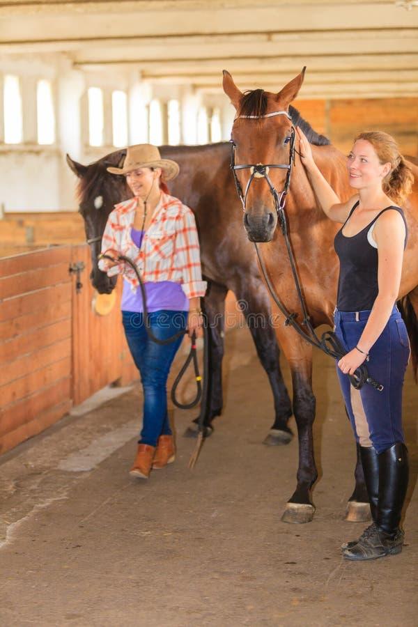 走与马的女牛仔和骑师在槽枥 免版税图库摄影