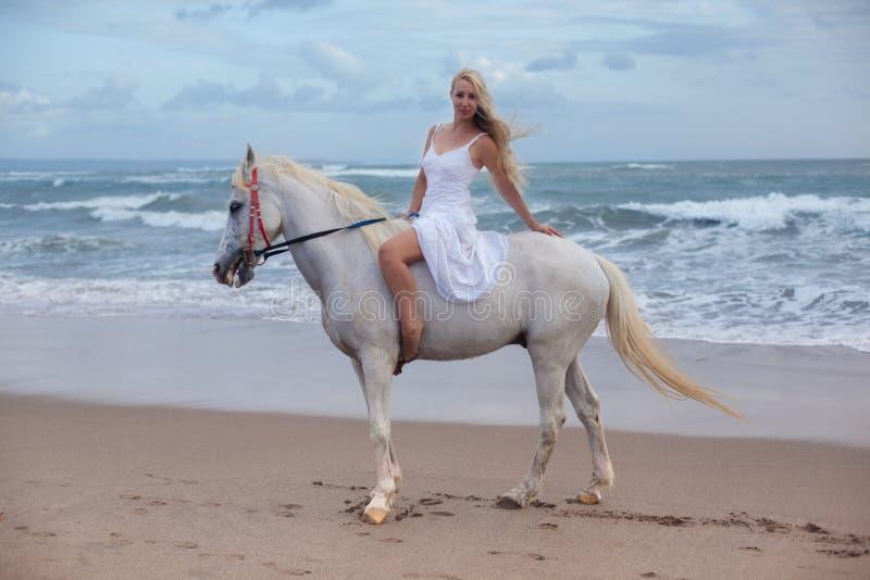 走与马的性感的少妇在海滩,马背 免版税库存照片