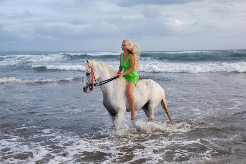 走与马的性感的少妇在海滩,马背 免版税库存图片