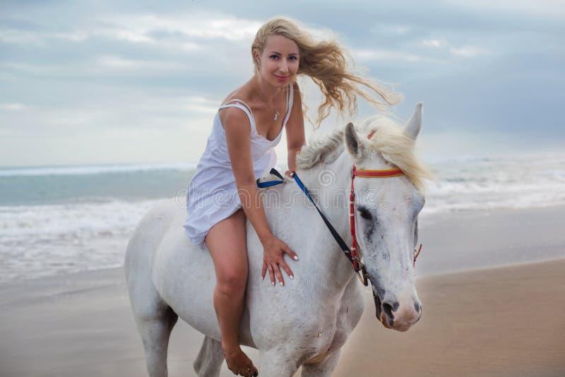 走与马的美丽的少妇在海滩,马背 库存照片