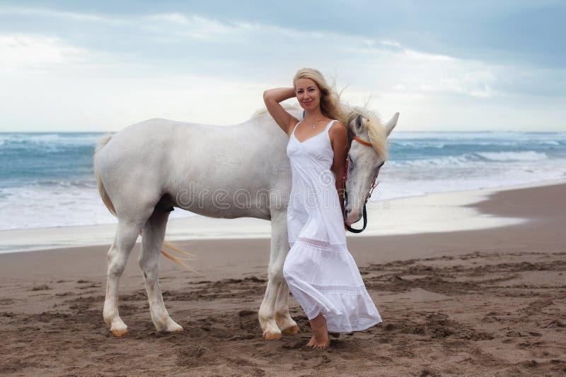 走与马的美丽的少妇在海滩,马背 免版税库存照片