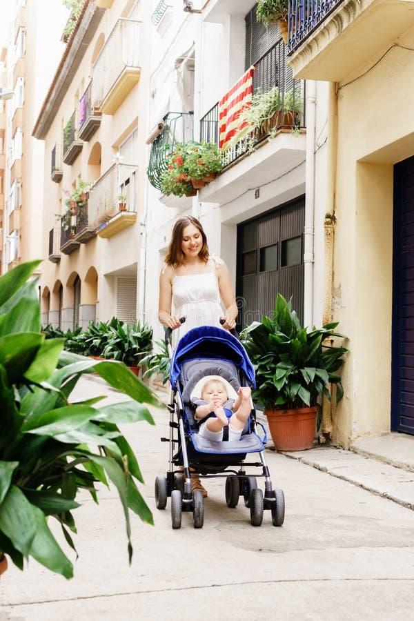 走与婴孩摇篮车的母亲 免版税库存图片
