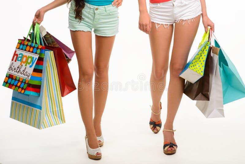 走与购物袋的女孩的典雅的腿 免版税库存照片