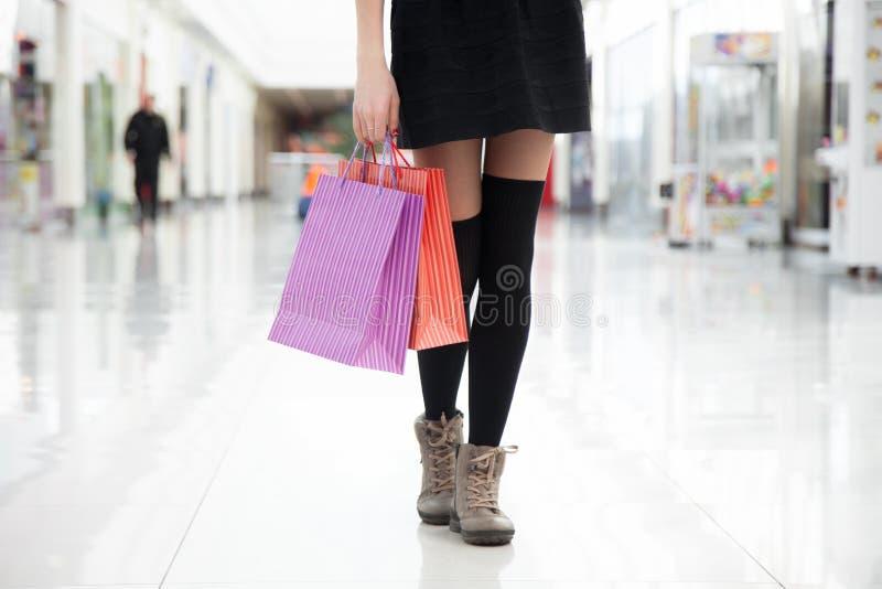 走与购物袋,关闭女性腿 库存图片