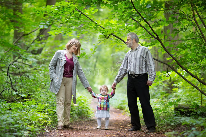 走与他们的小孙女的年轻祖父母 库存照片