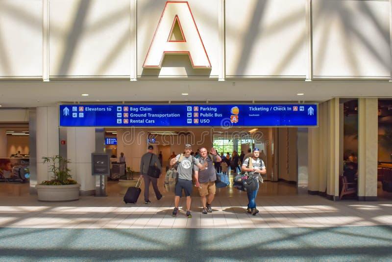 走与bagagge的人们在终端A地区在奥兰多国际机场 库存照片