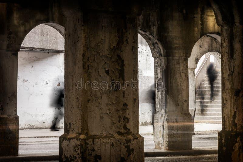 走从一条地下城市街道的一层楼梯的人们 图库摄影