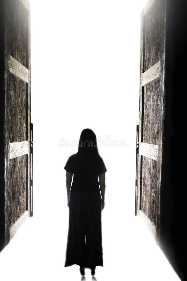 走入光的妇女通过开放大门 免版税库存照片