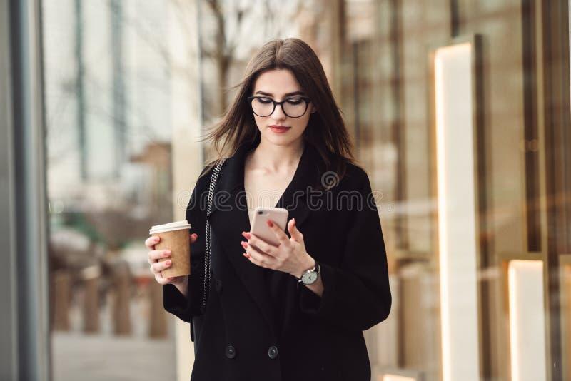 走到与咖啡一起使用和发短信在电话的美丽的女商人戴着眼镜户外 免版税图库摄影