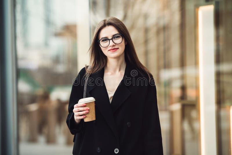 走到在城市街道上的办公室的美丽的白种人女商人有咖啡杯戴着眼镜的 图库摄影