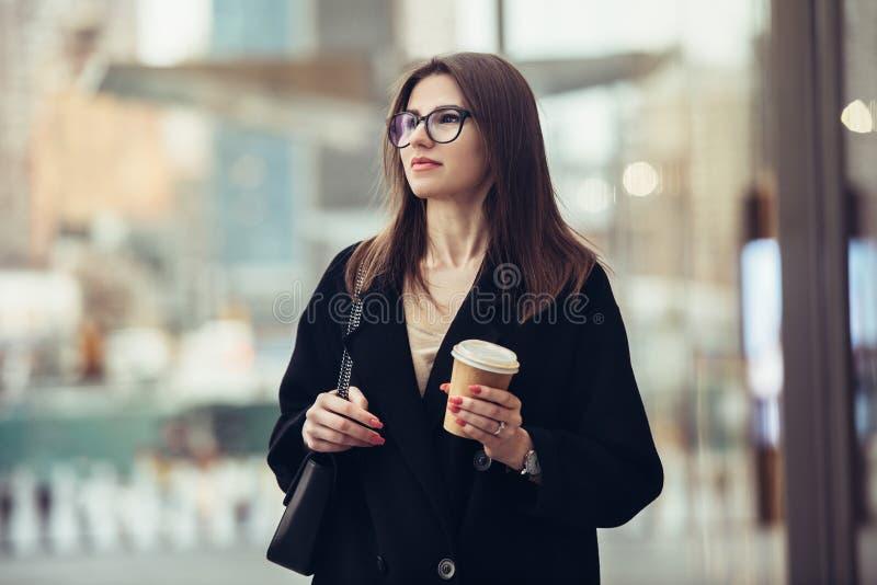 走到在城市街道上的办公室的美丽的白种人女实业家有咖啡杯佩带的镜片的 免版税库存图片