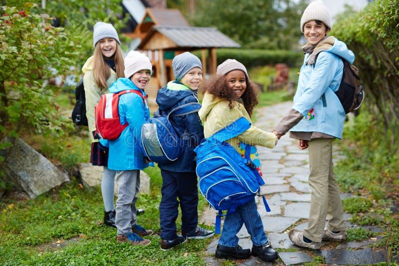 走到学校的小组愉快的孩子在秋天 免版税库存照片