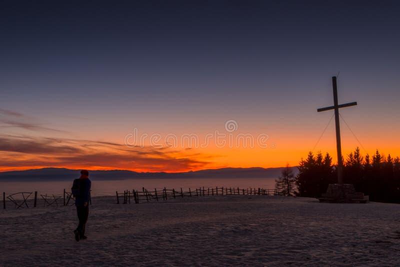 走到山Schoeckl山顶十字架的远足者与日落的 免版税库存图片