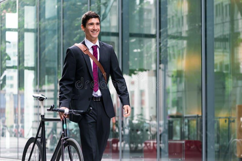 走到工作的愉快的活跃年轻人在自行车commutin以后 图库摄影